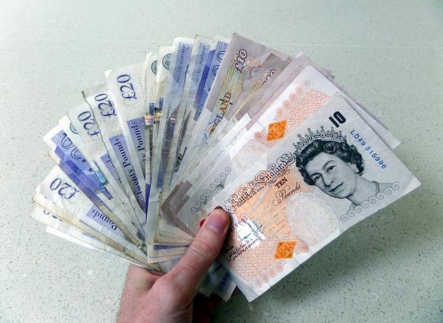 vějíř britských bankovek v ruce